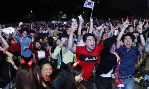 Cổ động viên Hàn Quốc hò reo ăn mừng sau chiến thắng của đội nhà hôm 27/6. Ảnh: AFP.