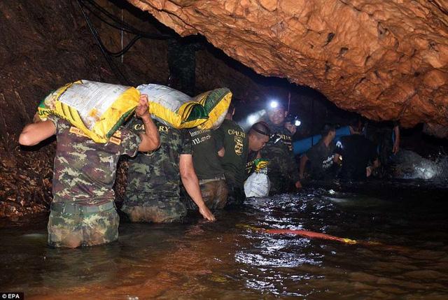 Binh sĩ Thái Lan vận chuyển trang thiết bị nhu yếu phẩm vào trong hang để lập trạm cứu hộ tạm. (Ảnh: EPA)