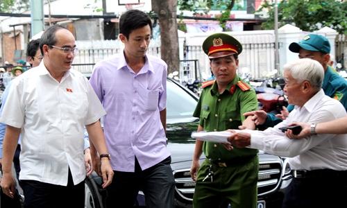 Người dân chào đón Bí thư Thành ủy Nguyễn Thiện Nhân (trái) đến buổi tiếp xúc cử tri hôm 20/6. Ảnh: Phạm Duy.