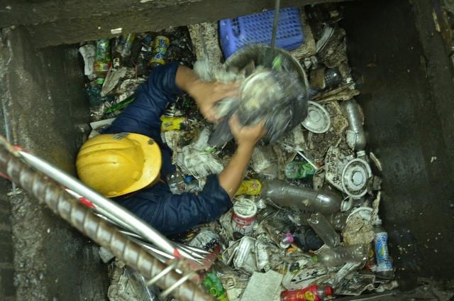 Công nhân vớt rác dưới cống đường Nguyễn Hữu Cảnh (ảnh: Đình Thảo)