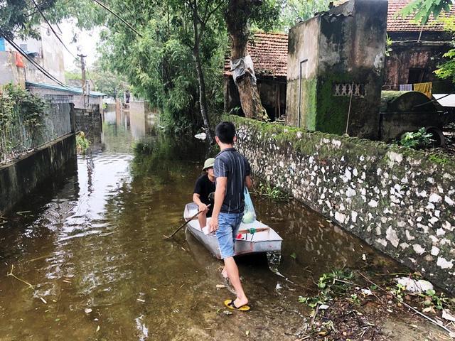 Một số hộ dân nước chưa rút, phải chèo thuyền ra bên ngoài, chờ người thân tiếp ứng lương thực vào bên trong