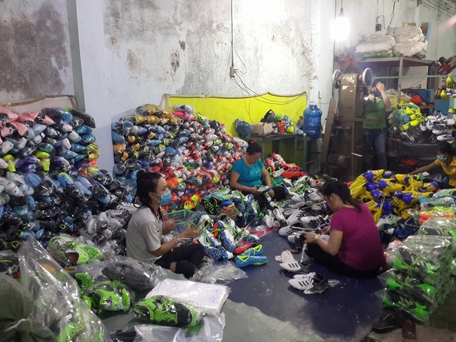 Các công nhân đang sản xuất hàng ngàn đôi giày thể thao nghi giả nhãn hiệu các thương hiệu nổi tiếng