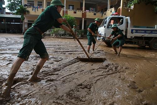 Bộ đội biên phòng dọn vệ sinh tại thị trấn Mường Xén (Kỳ Sơn) sau khi lũ rút. Ảnh: Nguyễn Hải.