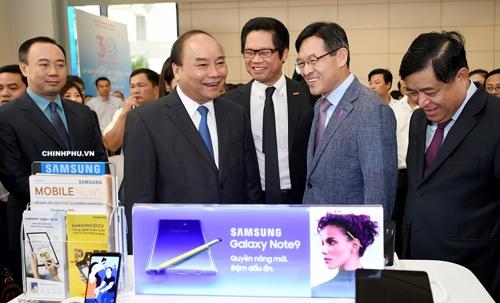 Thủ tướng Nguyễn Xuân Phúc và Bộ trưởng Nguyễn Chí Dũng thăm quan gian hàng của một doanh nghiệp FDI. Ảnh: VGP.
