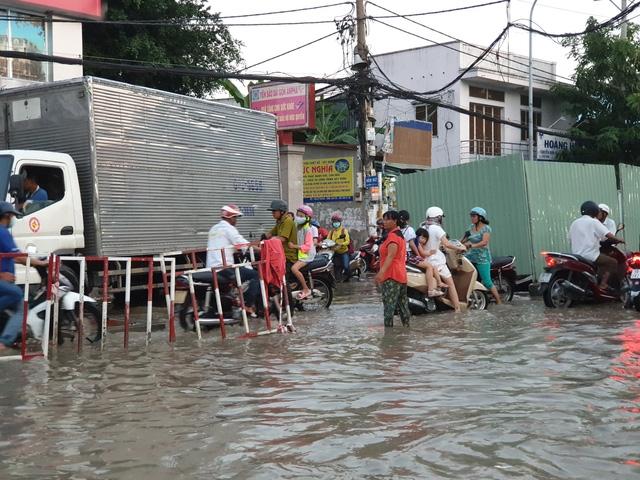 Trong ảnh là chị Nga (làm nghề bán bánh lọt) khi đi bán ngang qua đây thấy cảnh ngập nước, kẹt xe nên bỏ cả xe bánh chạy ra điều tiết giao thông, đẩy xe giúp dân