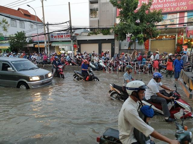 Triều cường dâng cao gây ngập đường Huỳnh Tấn Phát khiến người dân gặp nhiều khó khăn khi di chuyển qua đây