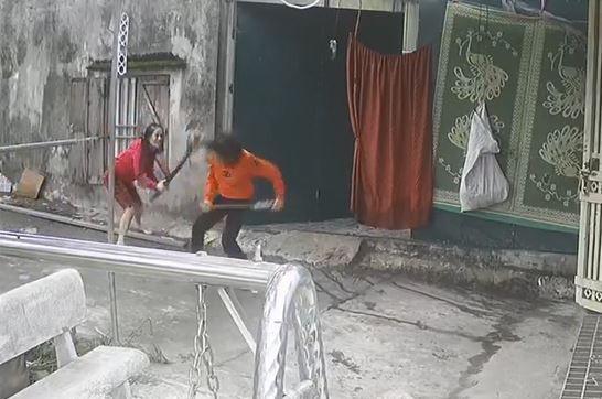 Bà Bùi Thị Vân (áo vàng) bị người hàng xóm dùng gậy đánh vào đầu phải nhập viện điều trị (ảnh cắt từ clip)