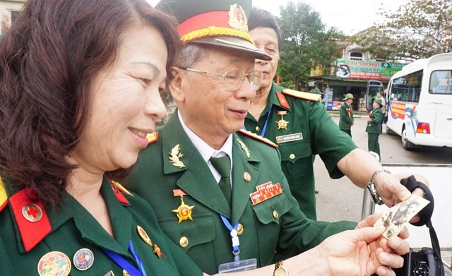 Đại tá Nguyễn Văn Thục (ở giữa) và món quà đặc biệt được nhận từ người đồng đội cũ. Đó là bức ảnh ông và con trai, kỉ vật người lính mang theo ra chiến trường