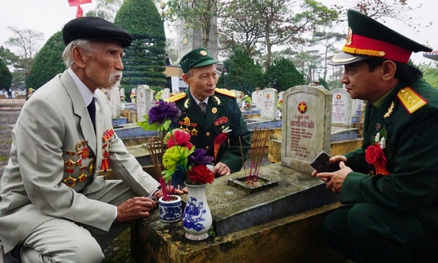 Cựu binh Lê Văn Tuấn (ngoài cùng bên trái) trước phần mộ của người em trai mà gia đình, họ tộc đã dốc lòng tìm kiếm hàng chục năm qua