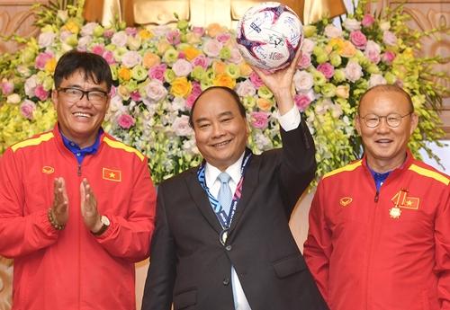 Thủ tướng Nguyễn Xuân Phúc nhận quả bóng đội tuyển VN tặng trong cuộc gặp ban huấn luyện và các cầu thủ ngày 21/12/2018. Ảnh: VGP