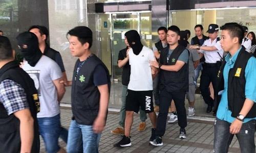 Hai người đàn ông nhập cư bất hợp pháp vào Macau, trong đó có một người quốc tịch Việt Nam, bị giải tới cơ quan công tố. Ảnh: Macau News.