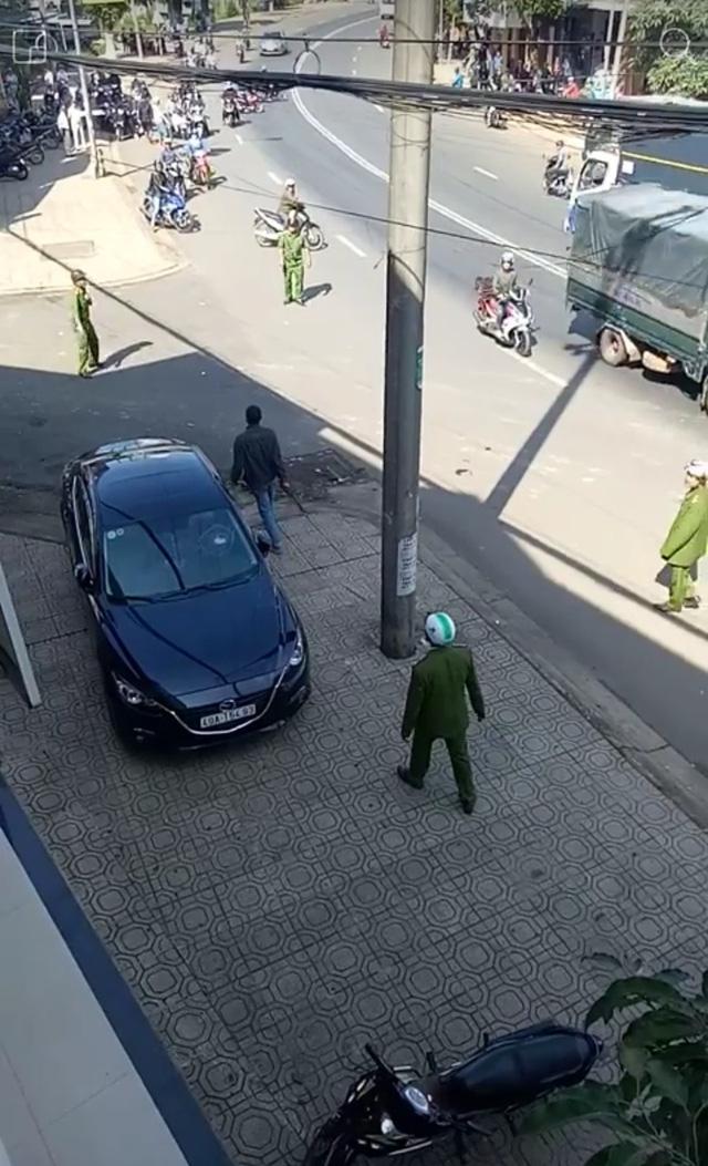 Đối tượng đập phá chiếc xe bên đường, sau đó tiếp tục cầm dao rượt đuổi lực lượng công an (ảnh cắt từ clip)