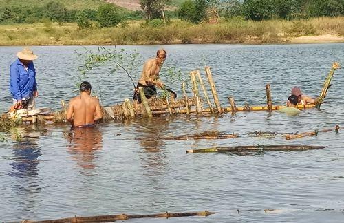 Người dân phường Hương Vân tự tháo dỡ hàng rào cọc tre trên sông Bồ. Ảnh: Đ.N