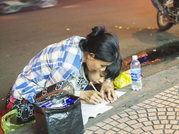 Bức ảnh mẹ cầm tay con viết ở vỉa hè chợ Bến Thành lay động ngàn trái tim - Ảnh 1.