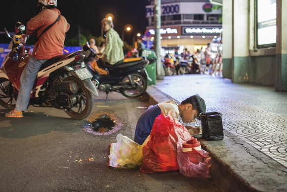 Bức ảnh mẹ cầm tay con viết ở vỉa hè chợ Bến Thành lay động ngàn trái tim - Ảnh 2.