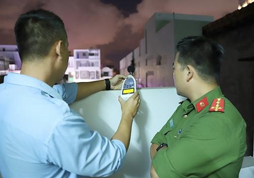 Nhân viên quan trắc môi trường và cảnh sát môi trường phối hợp đo đạc tiếng ồn của phòng trà ca nhạc trên đường Lê Duẩn. Ảnh: Nguyễn Đông.