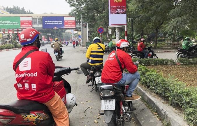 Nhiều tài xế xe ôm công nghệ đứng trước cổng Đại học Công đoàn sáng 2/1. Ảnh: Hoàng Phương