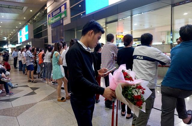 Có chàng trai ôm bó hoa tươi chờ đợi bạn.