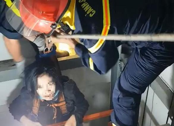 Giải cứu cô gái mắc kẹt trong thang máy bị rơi - Ảnh 1.