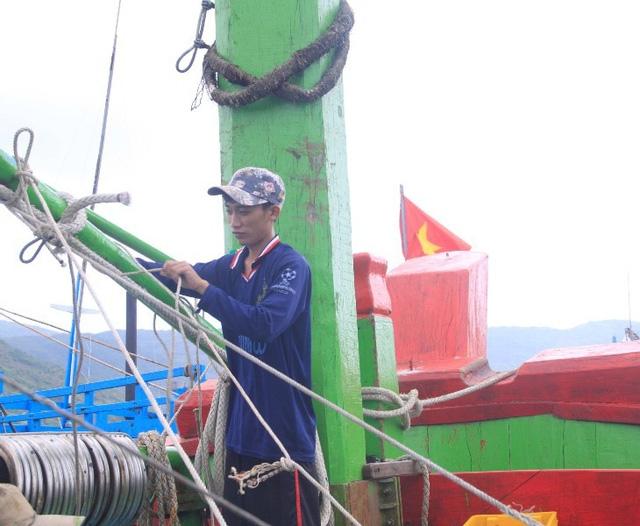 Thuyền viên kiểm tra cột giằng các thiết bị trên tàu cho an toàn trước khi tàu nổ máy khởi hành ra khơi đánh bắt.