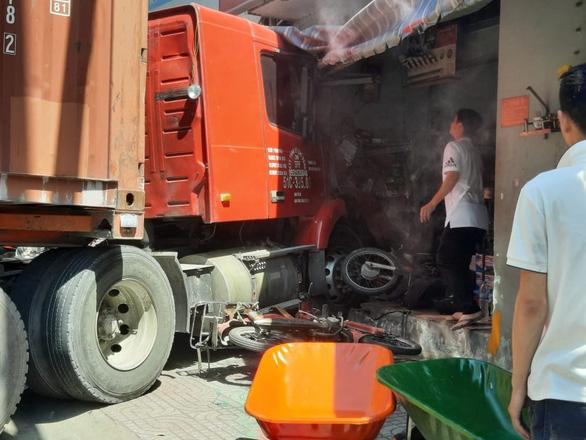 Xe container lao thẳng vào nhà dân ở quận 7, cuốn nhiều xe máy, 1 người chết - Ảnh 1.