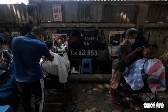 Tiệm cắt tóc vỉa hè, salon tóc đông kín khách ngày đầu mở lại - Ảnh 2.