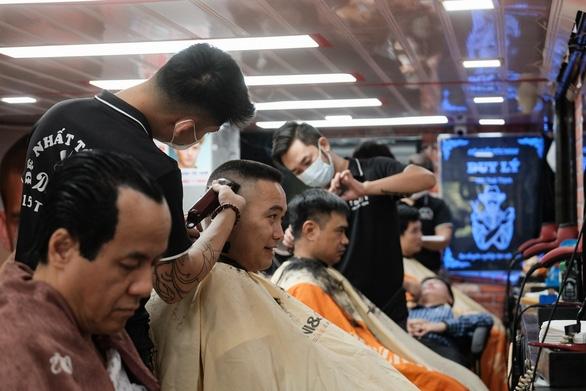 Tiệm cắt tóc vỉa hè, salon tóc đông kín khách ngày đầu mở lại - Ảnh 4.