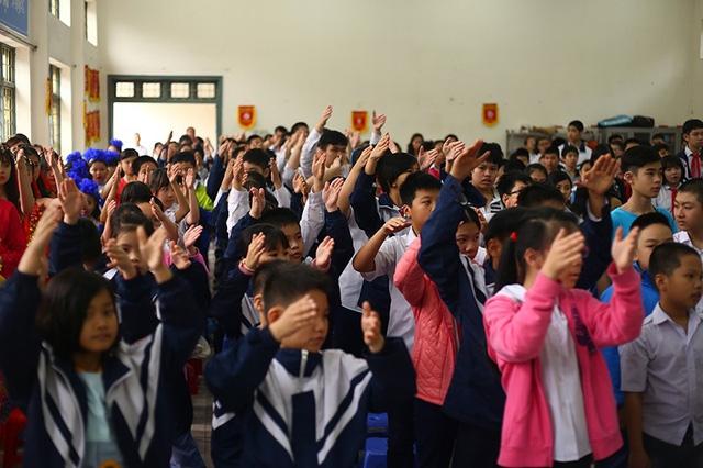 """Các học sinh khiếm thính của trường Phổ thông cơ sở Xã Đàn hát Quốc ca, Đội ca trong lễ chào cờ bằng """"thủ ngữ"""" (ngôn ngữ ký hiệu)"""