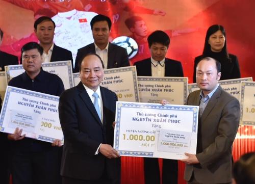 Thủ tướng trao kinh phí từ đấu giá bóng, áo của đội U23 cho 20 huyện nghèo. Ảnh:VGP/Nhật Bắc