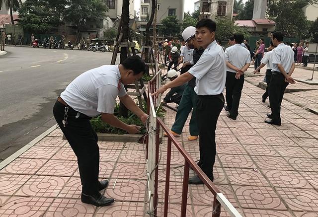Lực lượng chức năng vất vả tháo tháo bỏ hàng rào sắt chắn giữa hai dự án