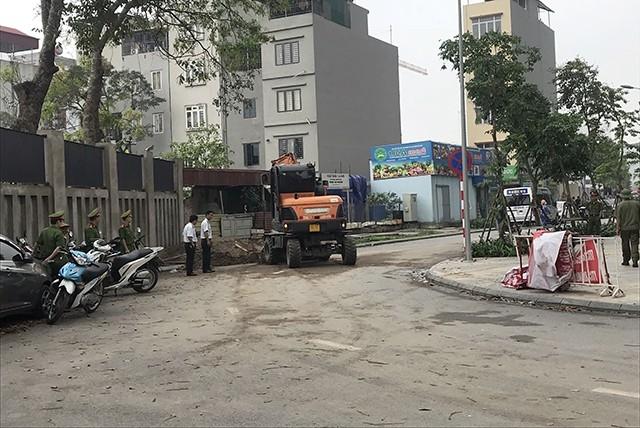 Lực lượng chức năng quận Bắc Từ Liêm mang máy cẩu đến hiện trường để giải tỏa ghế đá và đất cát chắn đường đi trong khu đô thị